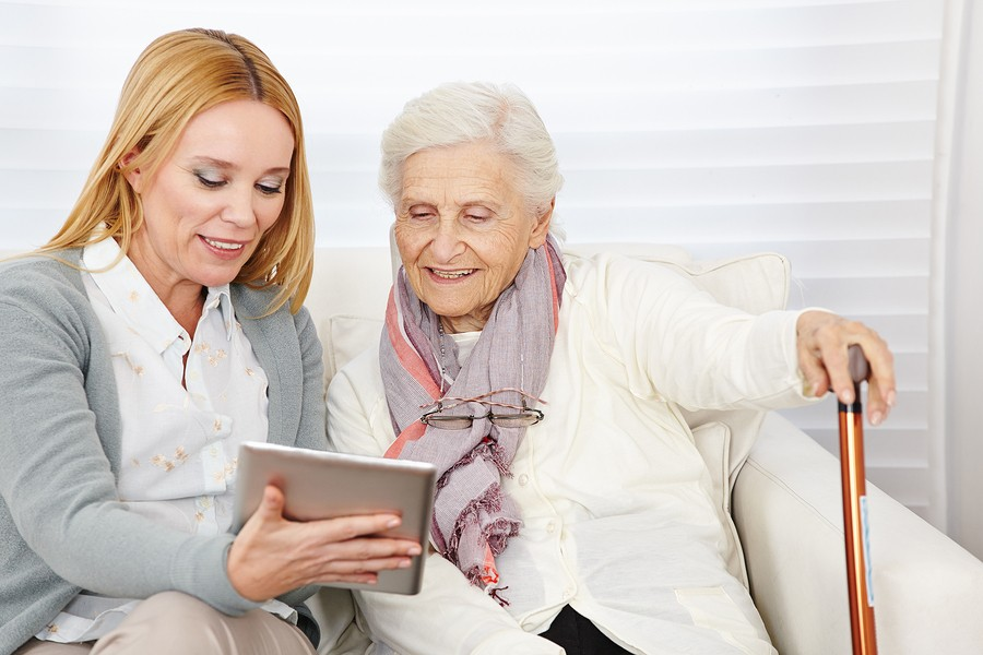 Woman giving senior woman introduction to internet with a tablet