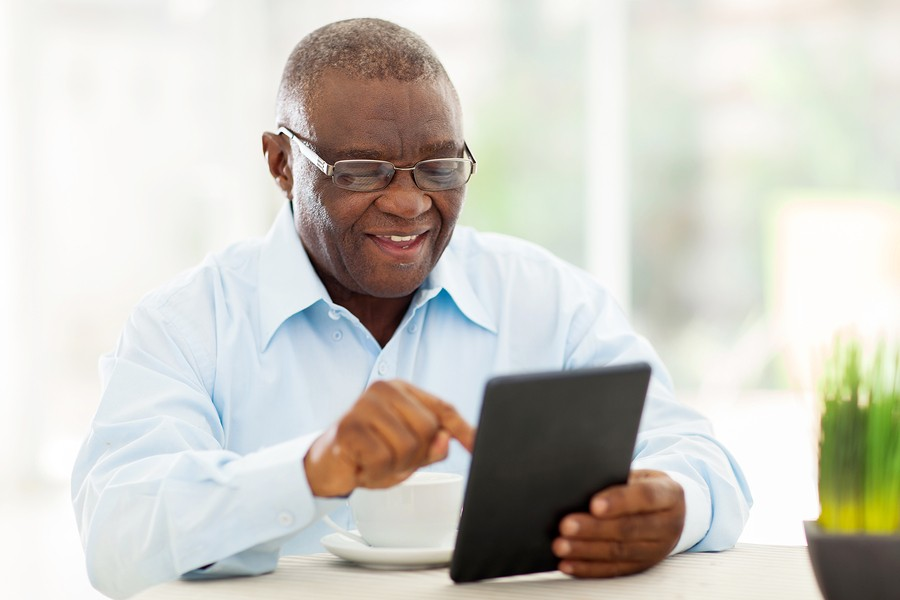 cheerful senior african american man using tablet computer at ho